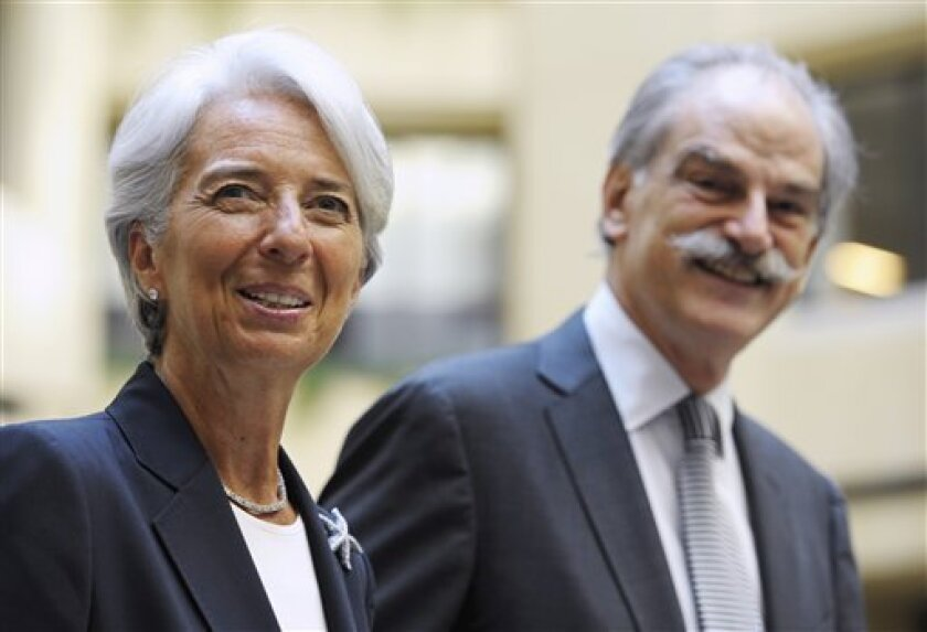 New IMF Managing Christine Lagarde, left, is met by IMF Acting Managing Director John Lipsky as she arrives at the IMF headquarters in Washington, Tuesday, July 5, 2011. (AP Photo/Cliff Owen)