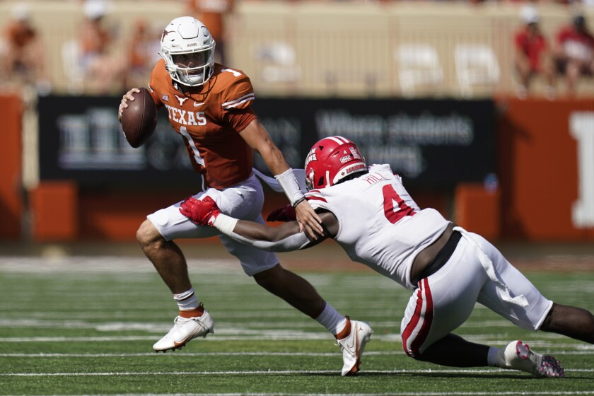 Texas quarterback Hudson Card (1) is pressured by Louisiana-Lafayette defensive lineman Zi'Yon Hill (4) during the first half of an NCAA college football game, Saturday, Sept. 4, 2021, in Austin, Texas. (AP Photo/Eric Gay)