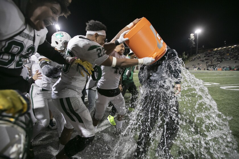 Oceanside players douse head coach David Rodriguez with water after winning the Division 1 football title game in 2019.