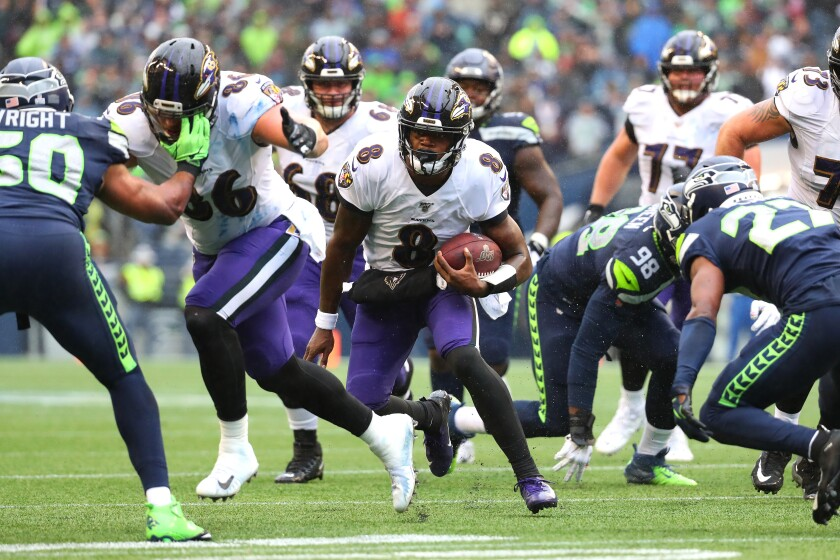 Baltimore Ravens quarterback Lamar Jackson runs with the ball against the Seattle Seahawks during the third quarter.
