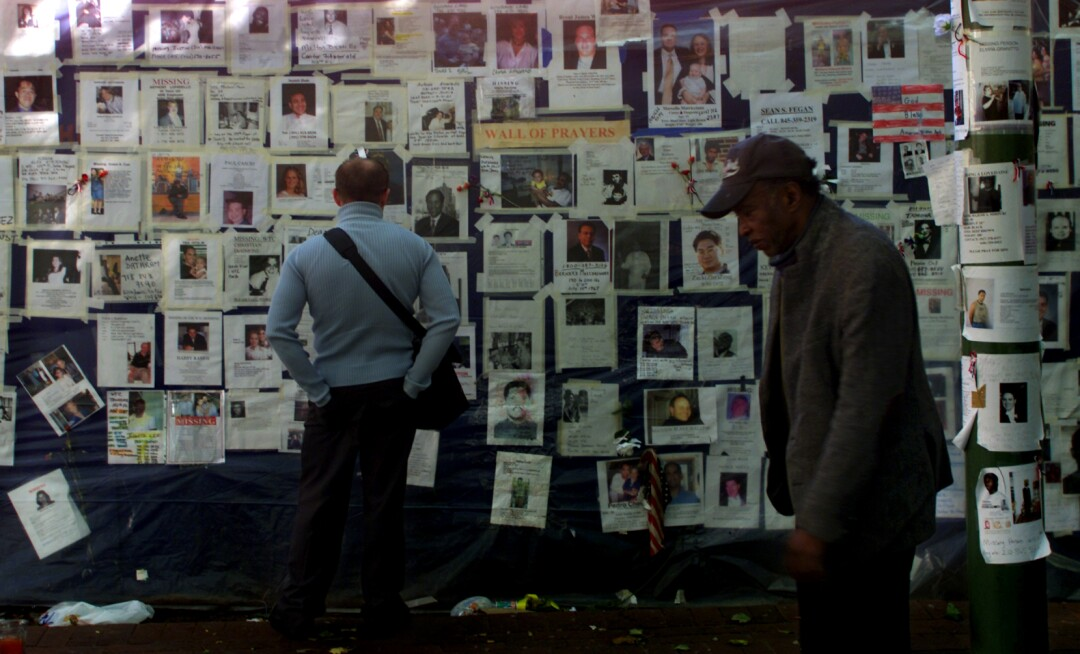 A man looks at missing-persons posters as another man walks past