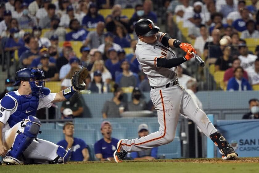 El pelotero de los Gigantes de San Francisco Wilmer Flores conecta un jonrón de dos carreras en el noveno inning de su juego de béisbol contra los Dodgers de Los Ángeles, el miércoles 21 de julio de 2021 en Los Ángeles. (AP Foto/Marcio Jose Sanchez)
