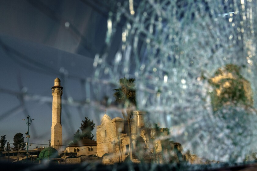 The minaret of the Al-Omari mosque and St. George Greek Orthodox church are reflected in the broken windshield of a vehicle sitting outside a synagogue in the mixed Arab-Jewish town of Lod, central Israel, Wednesday, May 26, 2021, in the wake of clashes between Arabs, police and Jews. The church shares a wall with a mosque and sits across from a synagogue in an area known as the triangle of religions. Like Jews and Arabs across the country, communities in Lod are on edge as the future of peaceful coexistence in mixed cities remains in question. (AP Photo/David Goldman)