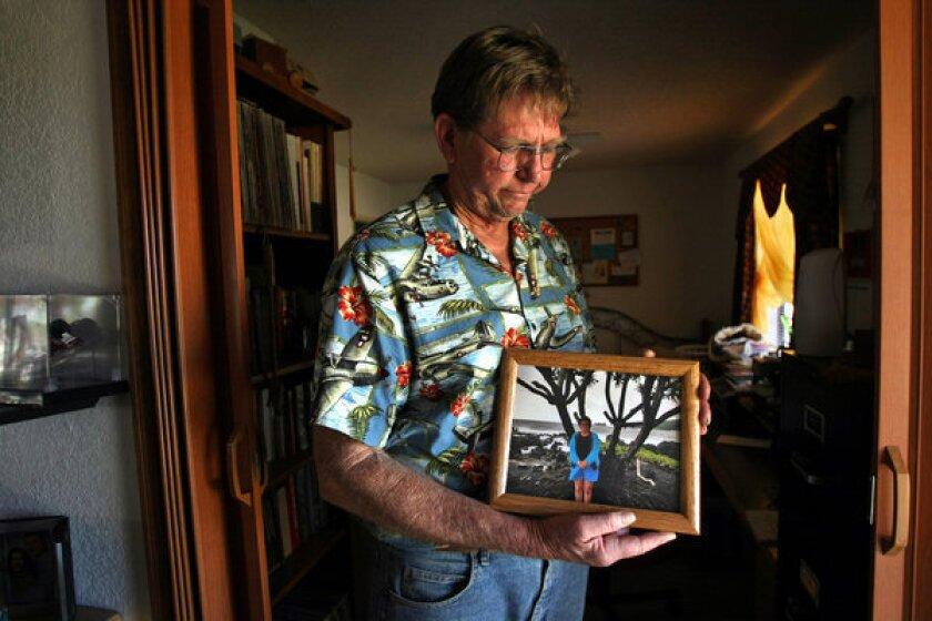 Ben Devitt holds a photo of his wife Pamela Devitt inside his home in Littlerock.