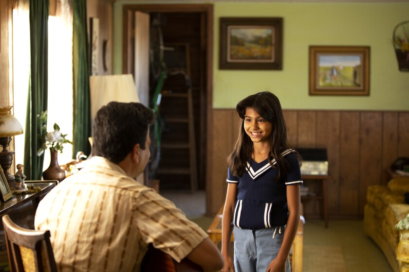 Young Selena, played by Madison Taylor Baez, smiles a gap-toothed grin at her father, seated and playing guitar.