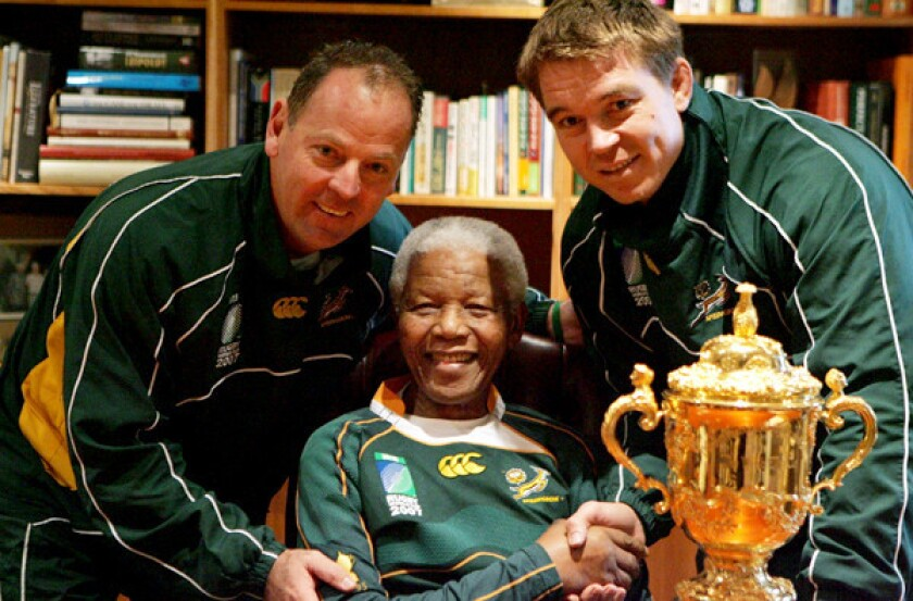 Nelson Mandela poses with South Africa Rugby Union Coach Jake White, left, and captain John Smit after the Springboks won the 2007 World Cup over England.