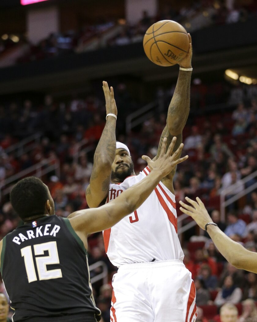 Houston Rockets' Josh Smith, right, passes the ball as Milwaukee Bucks' Jabari Parker (12) defends during the second half of an NBA basketball game Friday, Jan. 22, 2016, in Houston. (AP Photo/David J. Phillip)
