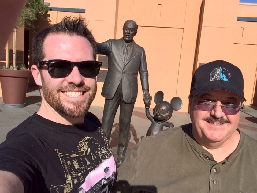 A father and son picture in front of a statue of Walt Disney and Mickey Mouse.