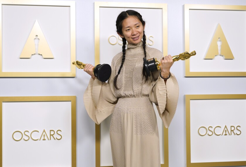 Chloé Zhao, in a gown with flowing sleeves, smiles as she holds an Oscar statuette in each hand.