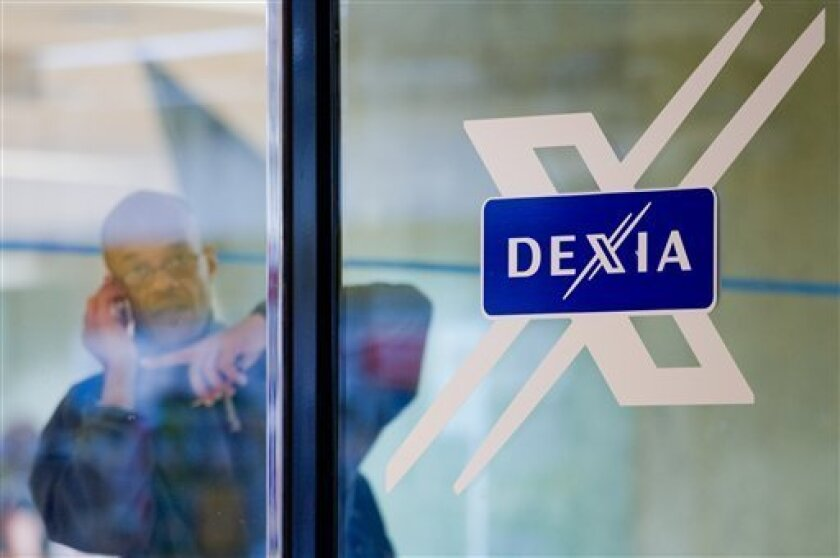 A man looks out of a door next to the Dexia logo at the corporate headquarters in Brussels on Tuesday, Oct. 4, 2011. France and Belgium were fighting to prevent Dexia from going under as investors grew increasingly worried over its ability to survive a renewed credit crunch. The two countries have promised Tuesday to prop up the bank and insure every cent of its deposits in response to a calamitous decline in the bank's share price over the past couple of days. (AP Photo/Geert Vanden Wijngaert)