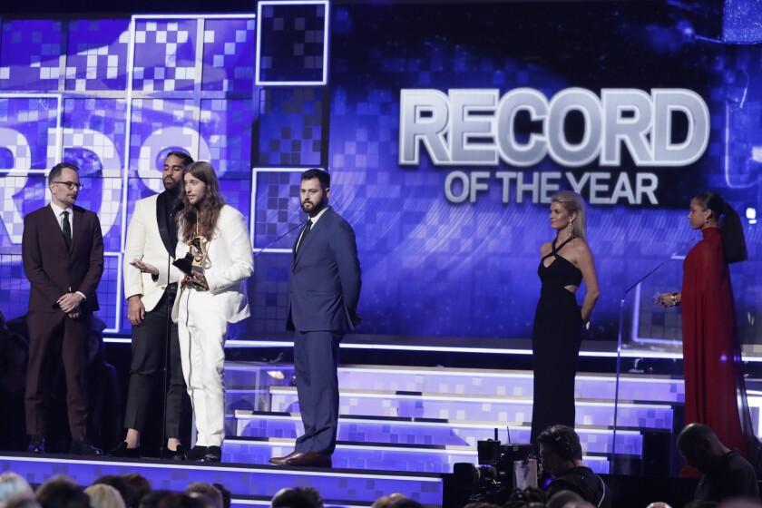 """Derek Ali y Ludwig Goransson aceptan el premio a la Grabación del Año por """"This is America"""" en el estrado del Grammy."""