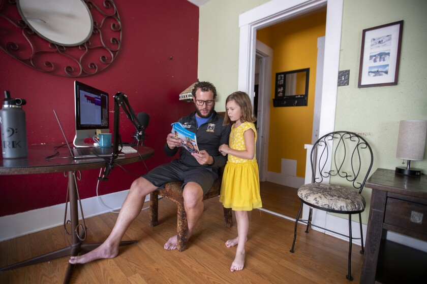 A child and her father read a book in front of their computer in a home.