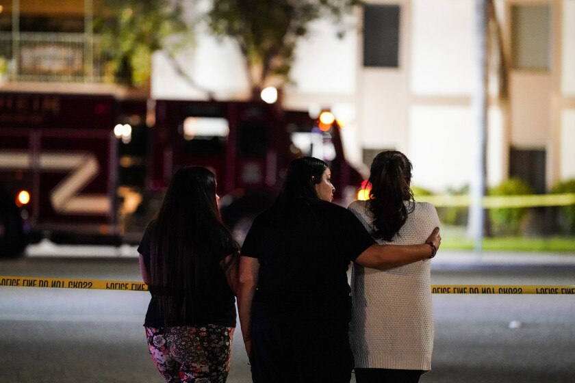 Residents watch as police respond to the scene of a multiple shooting