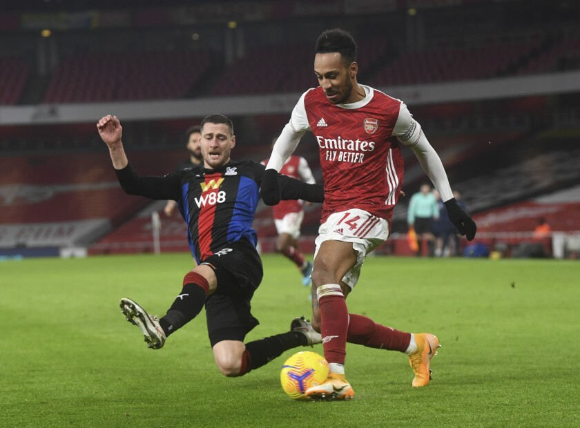 Crystal Palace's Joel Ward, left, tries to stop Arsenal's Pierre-Emerick Aubameyang, right, during the English Premier League soccer match between Arsenal and Crystal Palace at Emirates Stadium in London, Thursday, Jan. 14, 2021. (Neil Hall/Pool via AP)