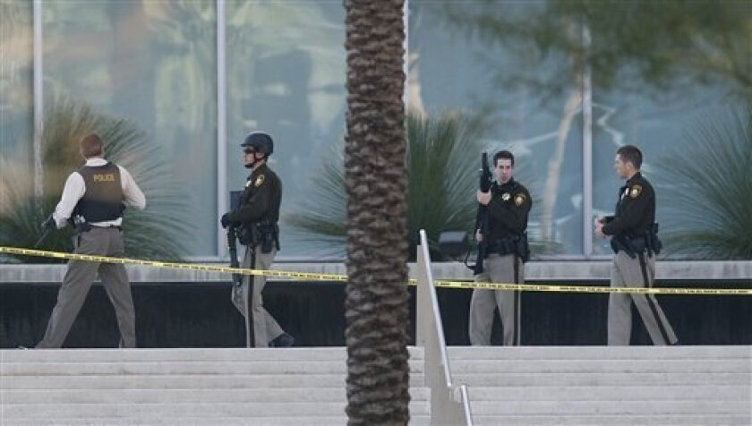 Law enforcement surround the Lloyd D. George federal courthouse building in downtown Las Vegas following a shooting Monday, Jan. 4, 2010, in Las Vegas. A courthouse security official and the suspect were killed, another officer is in serious condition. (AP Photo/Isaac Brekken)