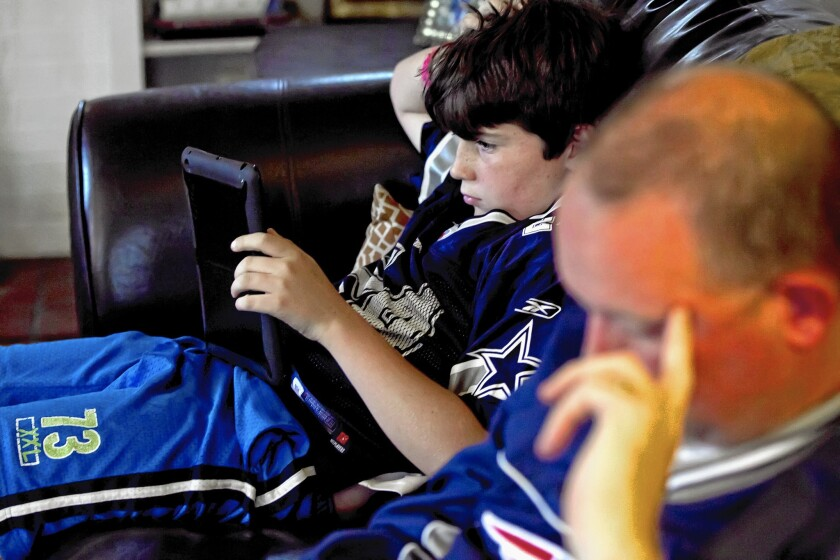 Streaming NFL games would allow Facebook to create content before and after the games. Above, 11-year-old Theo Kennedy looks at stats on an iPad while his father, Sean, looks at his stats on his iPhone as they watch NFL football.