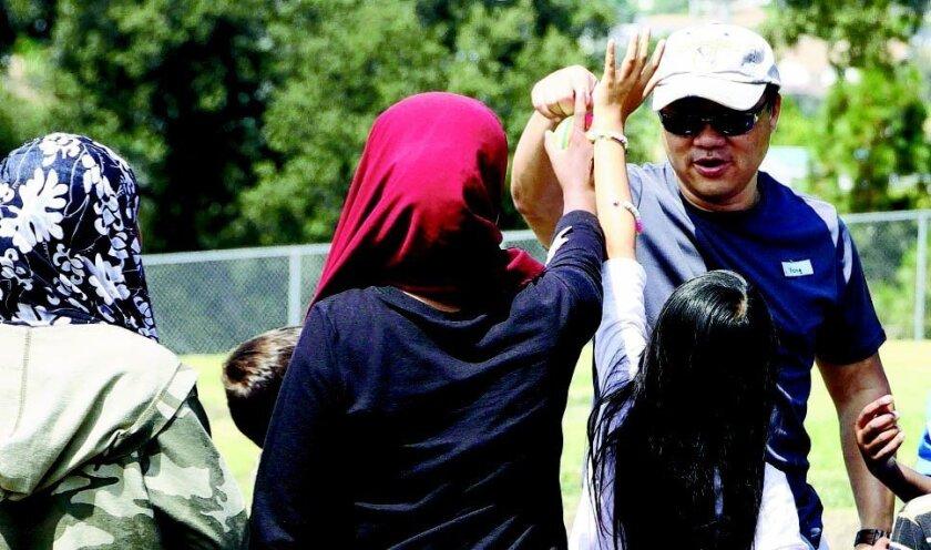 Yong Kim es uno de los voluntarios de San Diego Refugee Tutoring, aquí ayuda a unos niños refugiados a volar un papalote.Irasema Mayoral