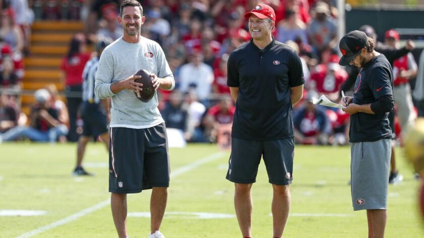 San Francisco 49ers coach Kyle Shanahan, left, watches practice with general manager John Lynch duri