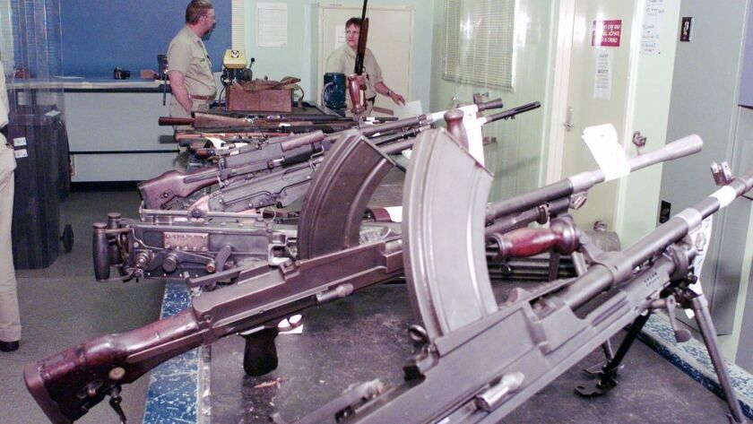 Police department workers in Sydney sort and catalog weapons handed in for refunds as part of the Australian government's money-for-guns plan in 1997. A new study raises doubt about whether the policy actually reduced gun deaths in the country.