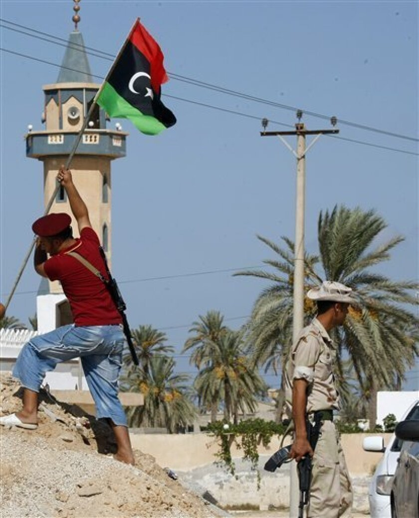 Libyan fighter plants the Libya's flag of the former rebels at a check point in Al Ajaylat, 120 km west of Tripoli, Libya, Wednesday, Sept. 7, 2011.  The new colours of the flag decorate a lot of streets and buildings after the six-month civil war that ended Gadhafi's 42-year rule and sent him into