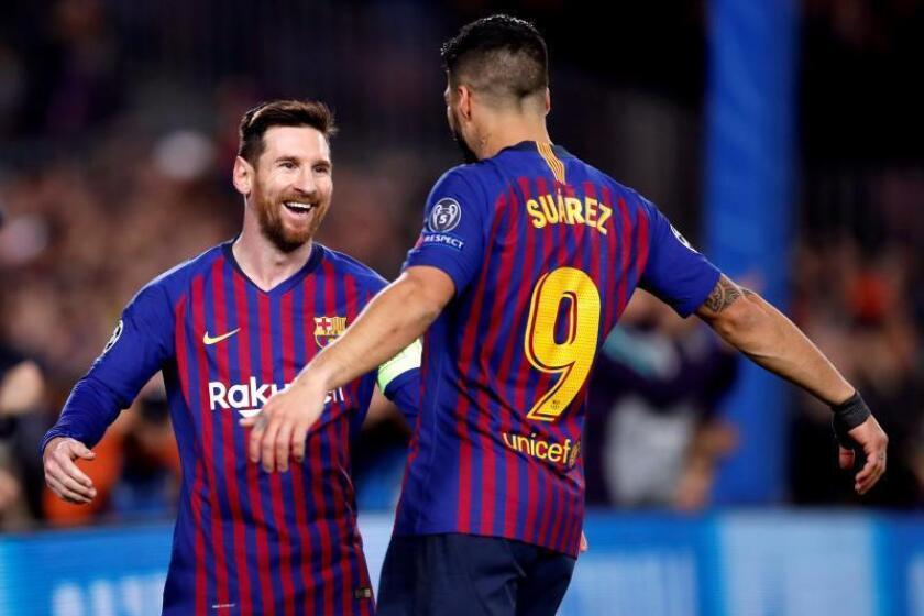 El delantero argentino del Barcelona Lionel Messi (i) celebra con su compañero Luis Suárez su primer gol ante el Olympique de Lyon durante el partido de vuelta de los octavos de final de la Liga de Campeones que se jugó en el Camp Nou, en Barcelona. EFE