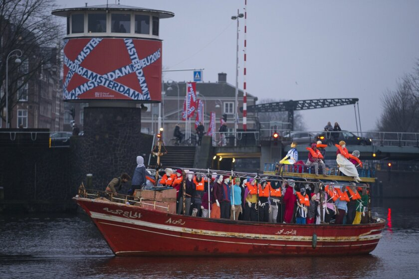 Activist with Amnesty International protest with a boat filled with mannequins wearing life vests as they protest against the ongoing refugee crisis prior to an informal meeting of EU Justice and Home Affairs ministers at the Maritime Museum in Amsterdam, Netherlands, Monday, Jan. 25, 2016. (AP Photo/Peter Dejong)