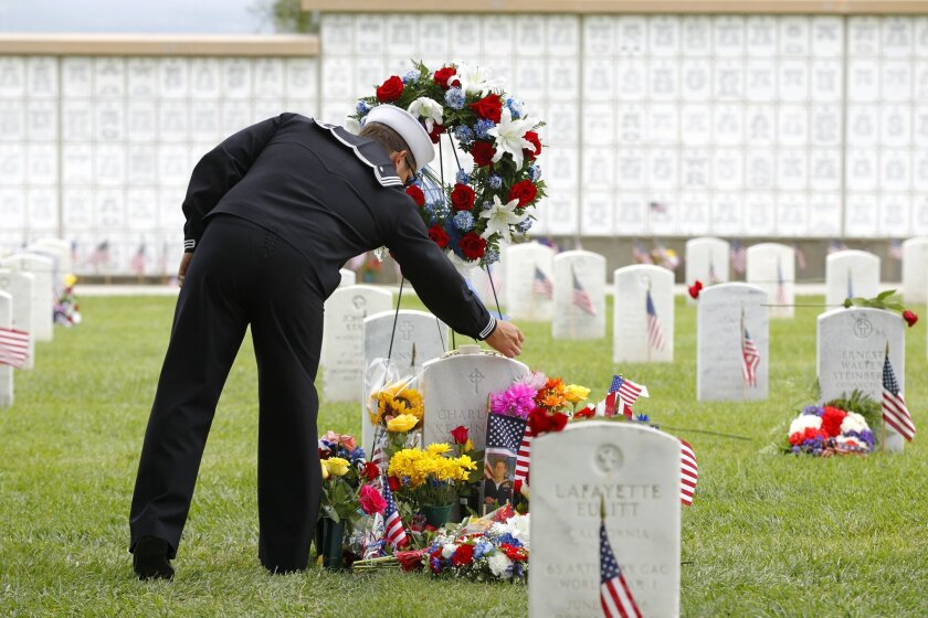 A Navy SEAL places a trident pin on the grave of fellow SEAL Charles Keating IV after the 116th Memorial Day Service at Fort Rosecrans National Cemetery. Keating, 31, was killed in action May 3rd in northern Iraq.