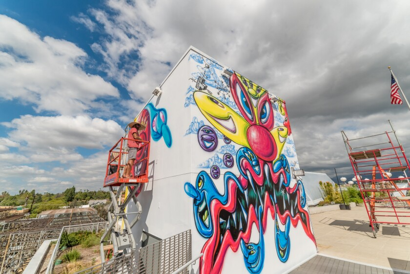 """Artist Kenny Scharf works on his mural """"Monstropolis"""" for the Art Center College of Design exhibition """"OutsideIn: The Ascendance of Street Art in Visual Culture."""""""