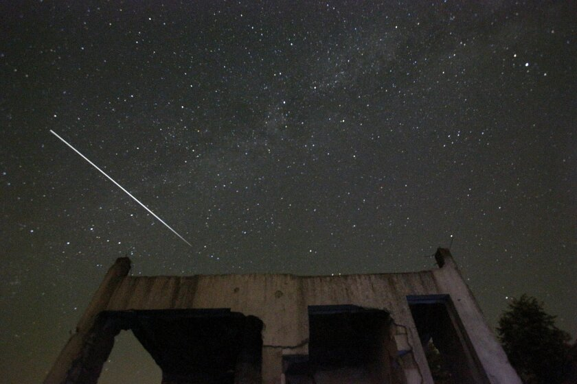 Stars and meteor streaks are seen behind a destroyed house, near Tuzla, Bosnia.
