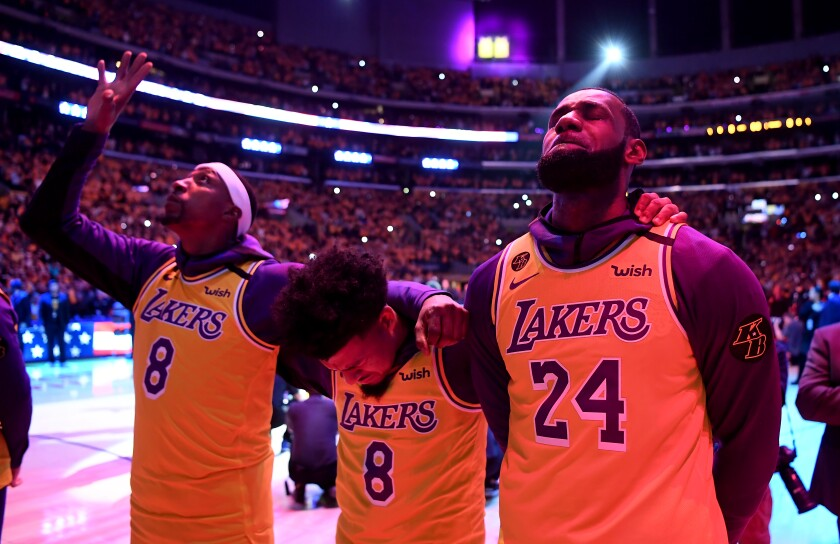 Kentavious Caldwell-Pope points skyward, and Quin Cook and LeBron James close their eyes, on the basketball court.