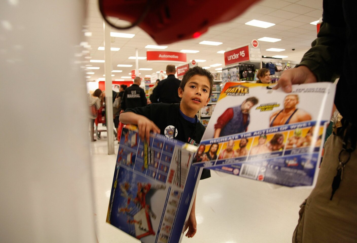 "Alex Corrales, 8, does a price check at Sports Arena Target while shopping for toys during the 22nd Annual ""Shop with a Cop""."