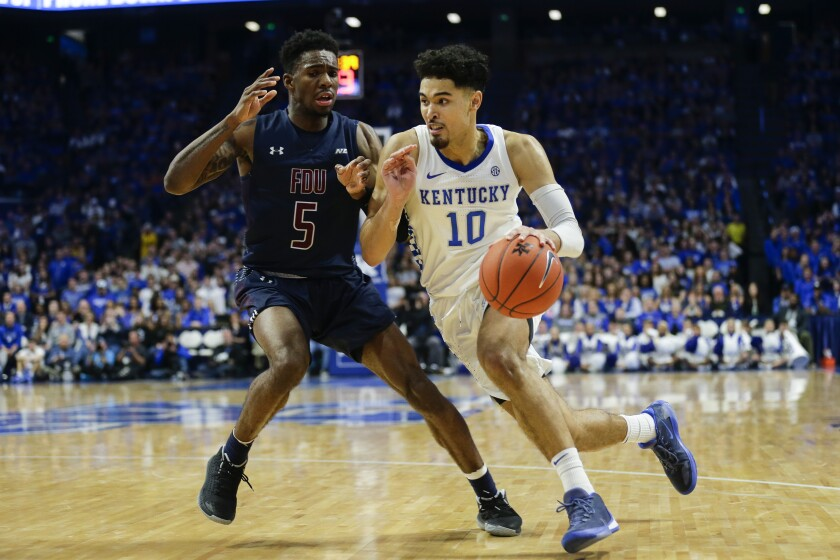 Johnny Juzang drives against Fairleigh Dickinson's Xzavier Malone-Key during a game for Kentucky.
