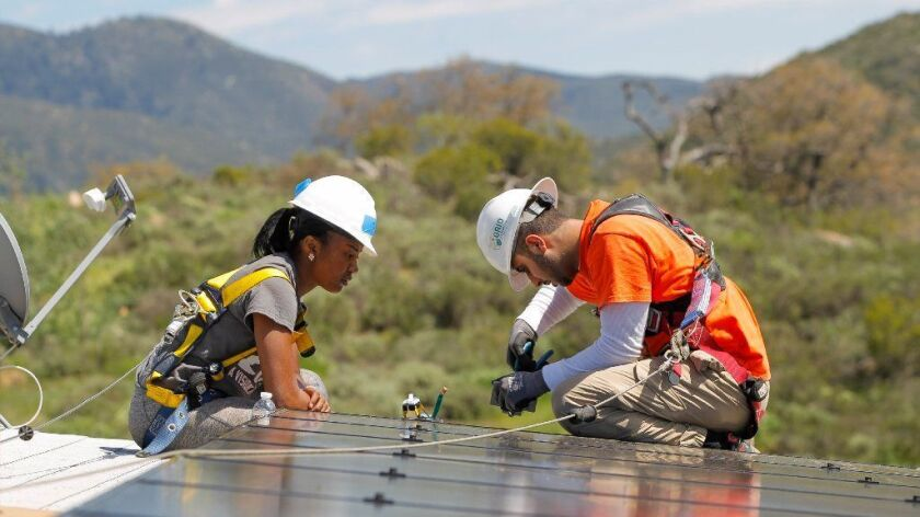 PAUMA VALLEY, March 15, 2017 | North Carolina University student Tatyana McAllister-Sanders, left, and Grid Alternative team leader Mohamed Hauter connect wires to solar panels.
