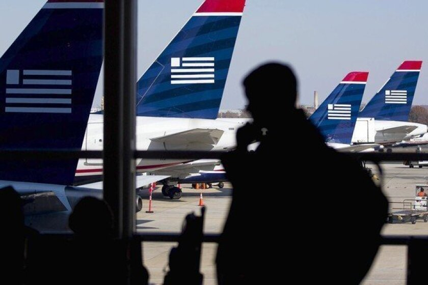 US Airways charges a $150 fee to change a flight reservation. Above, US Airways jetliners at Reagan National Airport in Washington.