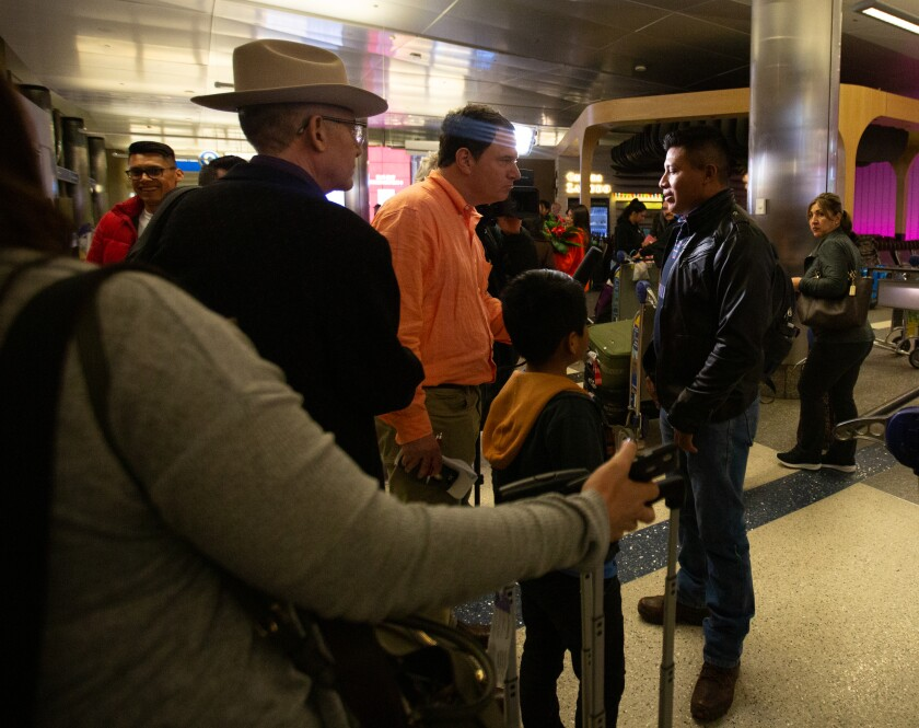 Byron Xol, 9, watches as his father, David Xol, right, is interviewed upon his return to the U.S.