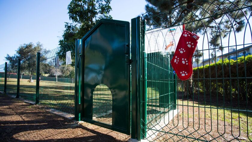 A stocking with dog treats hangs outside the entrance to the newly opened Veteran's Park Dog Park.