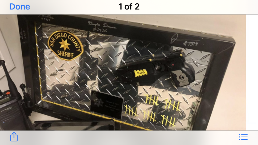 Plaque with a Taser, sheriff's patch and 25 tally marks