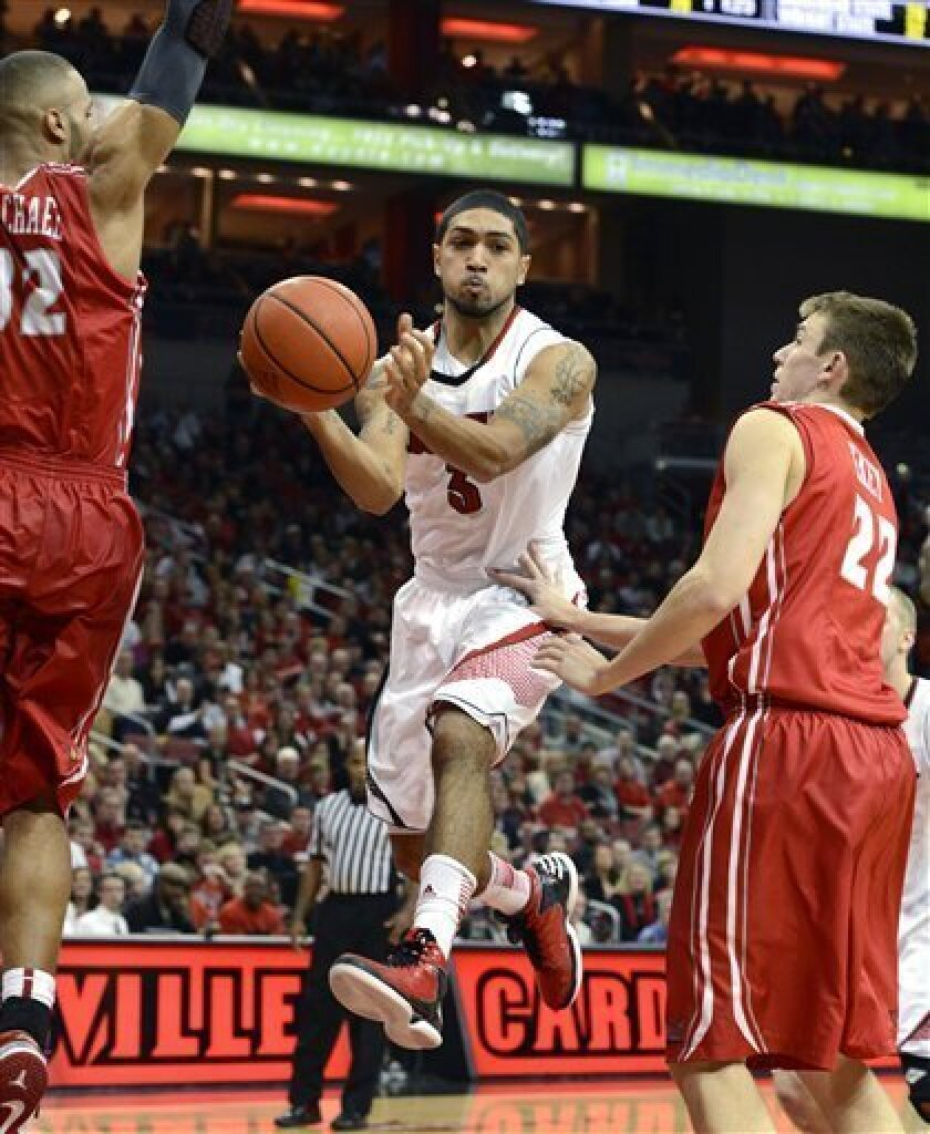 Louisville's Peyton Siva, center, passes the ball between the defense of Illinois State's Jackie Carmichael, left, and Jon Ekey during second half action of an NCAA college basketball game, Saturday, Dec. 1, 2012, in Louisville, Ky. (AP Photo/Timothy D. Easley)