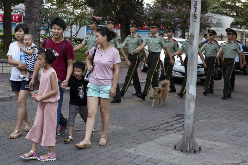 Chinese paramilitary policemen march past residents near the Philippines embassy in Beijing Tuesday, July 12, 2016. A tribunal ruled on a case raised by the Philippines in a sweeping decision Tuesday that China has no legal basis for claiming much of the South China Sea and had aggravated the seeth