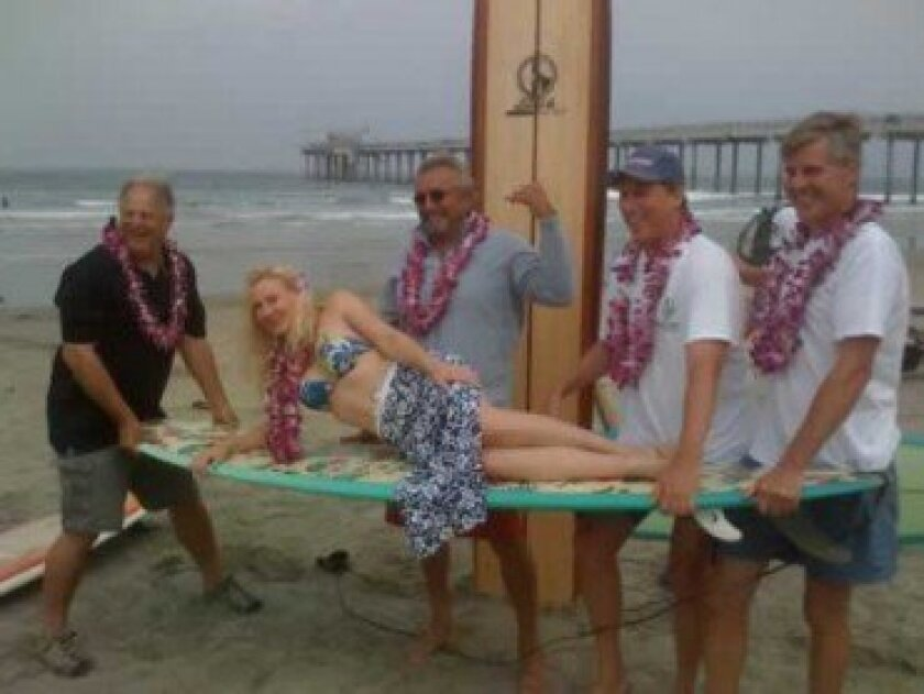 From left: Terry Rodgers, surf legend Mike Doyle, Steve Keane and event co-founder Sam Armstrong with Nicole DeBerg (lying on board) during a previous Luau and Longboard Invitational event. Courtesy