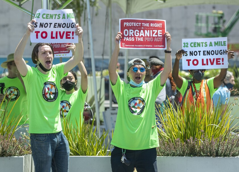 People in green shirts hold up protest signs.