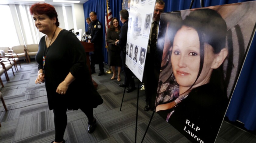 Gerilyn Olguin, mother of Lauren Olguin, walks past her photo at the conclusion of a press conference at the FBI Los Angeles field office regarding Sunday's arrest of fugitive Philip Patrick Policarpio, who was charged with murder in her shooting death.