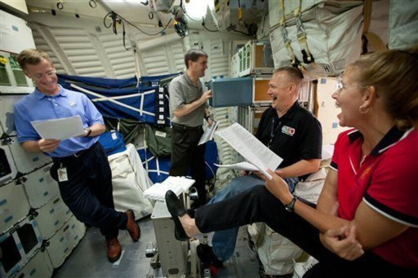 In this Wednesday, June 29, 2011 photo, the crew of STS-135, from left, Chris Ferguson, Rex Walheim, Doug Hurley and Sandy Magnus review procedures on the mid-deck of the Crew Compartment Trainer (CCT) II mockup as they train at the Johnson Space Center, in Houston. The training marked the crew's f
