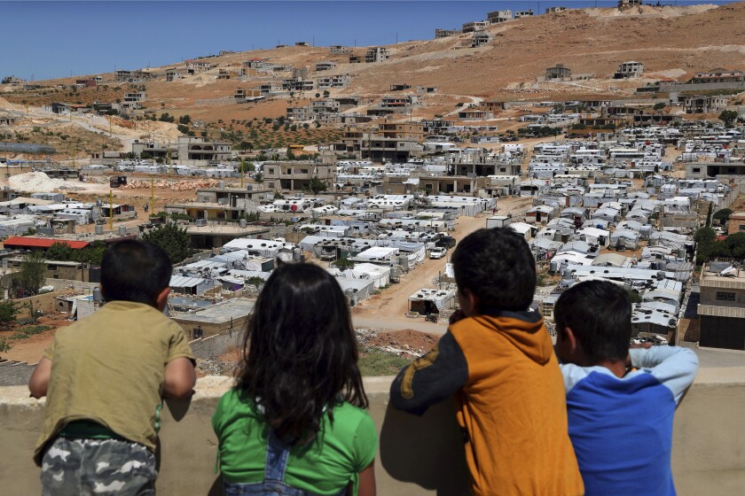 FILE - In this June 16, 2019, file photo, Lebanese children look from the rooftop of their home at a Syrian camp in the eastern Lebanese border town of Arsal. When dozens of heads of state convene for the annual ministerial meeting of the U.N. General Assembly, the lingering conflict in Syria is taking a back seat as tensions in the Persian Gulf and global trade wars take center stage. In its ninth year, many Syrians fear their country's unresolved war has become a footnote in a long list of world crises. (AP Photo/Bilal Hussein, File)