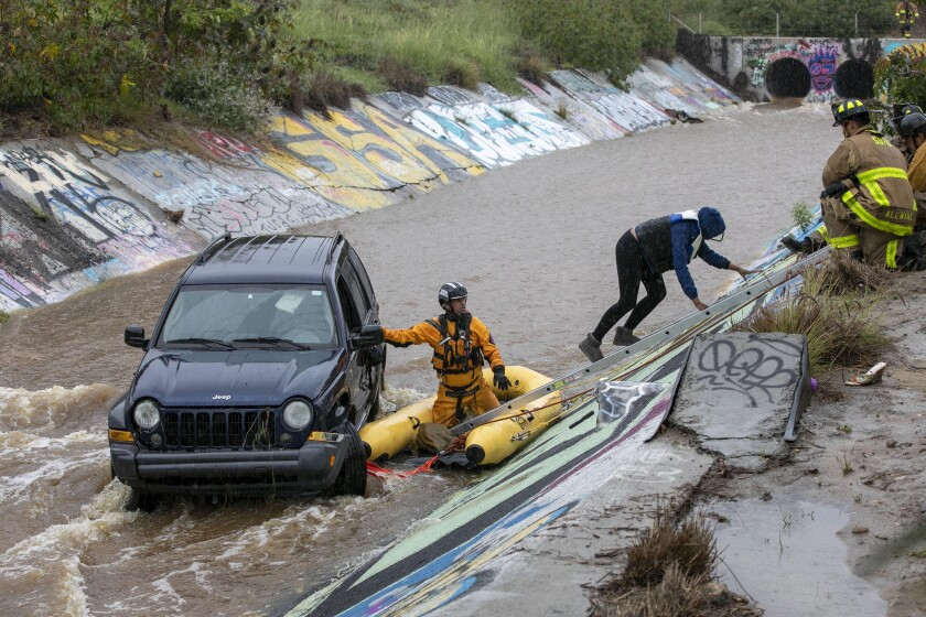 San Diego Fire-Rescue firefighters and lifeguards teamed up to get two people out of a Jeep that slid into the Chollas Creek drainage ditch at Highway 94 and Interstate 15 on Friday.