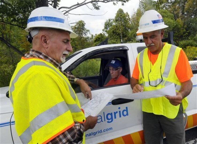 Line inspectors Paul Bonner, left, Tom Brondou ,center, and Roger Marocco all from Nationalgrid out of Utica, N.Y., check circut maps to check for power outages caused by Tropical Storm Irene in the town of Berne, N.Y., Thursday, Sept. 1, 2011. Utility companies continue to bring New York electricity customers back on line, but almost 182,000 are still blacked out four days after Irene pounded the state with drenching rains and high winds. (AP Photo/Hans Pennink)