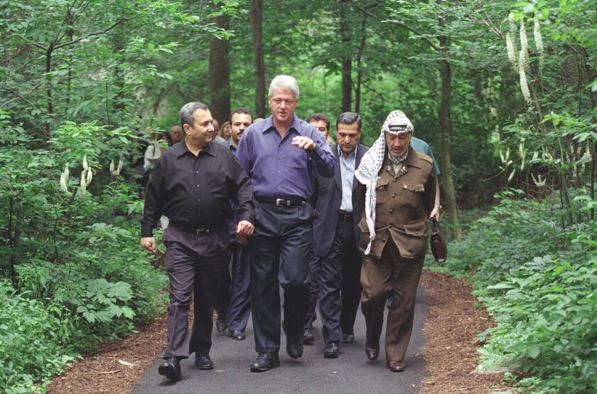 Bill Clinton and others walk on a footpath.