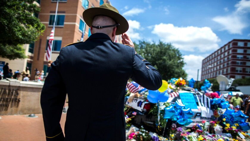 Retired Army Sgt. Chandler Davis pays his respects at a growing memorial in front of the Dallas police headquarters.