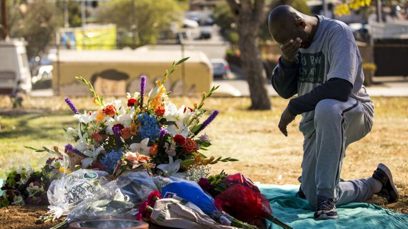 A man kneels by the site of a mass grave after an interfaith service for L.A. County's unclaimed dead in December 2017.