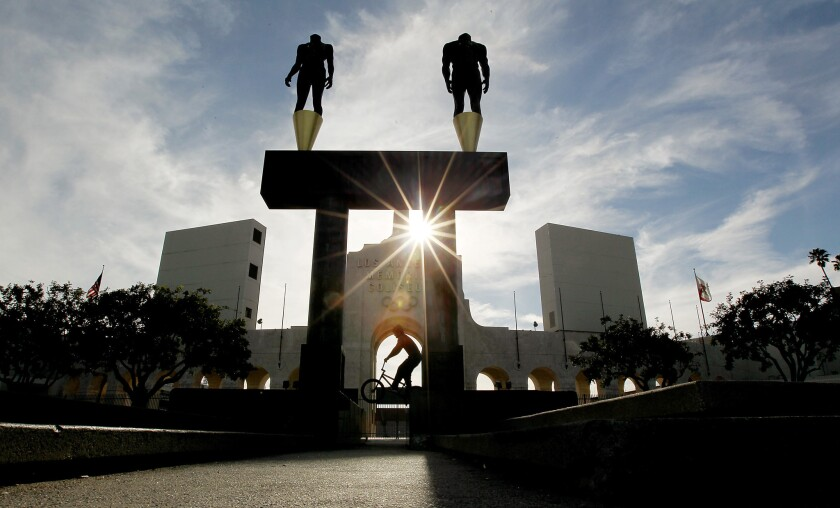 A bicyclist rides in front of the Los Angeles Memorial Coliseum on April 30.